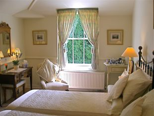 B&B accommodation twin bedroom. Guests occupying the twin bedroom have exclusive use of the beautifully hand painted private bathroom and private landing. Both rooms have views across pretty courtyard, gardens and south facing sun terrace